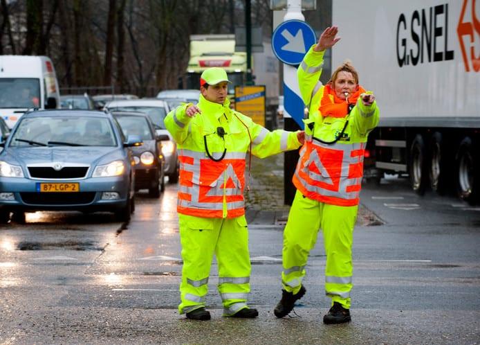 Twee verkeersregelaars in gekleurde pakken